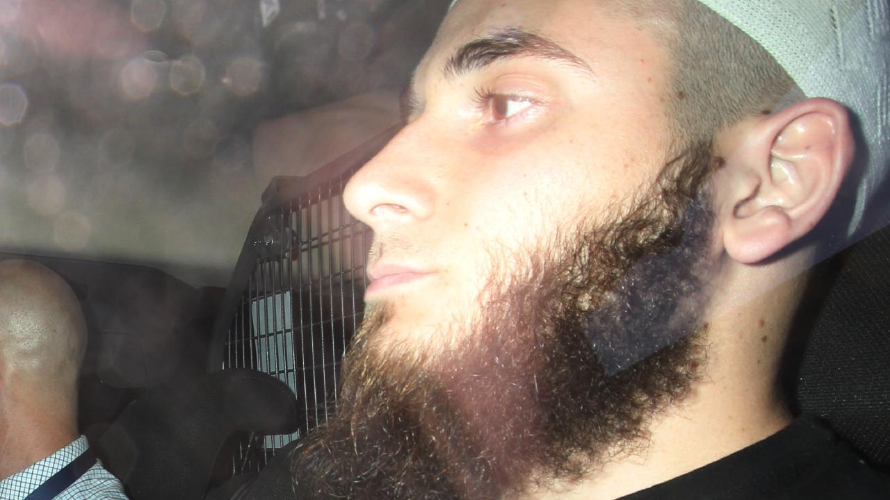 A picture of Agim Kruezi as he was  taken to Brisbane Watchhouse after he was arrested in terror-related raids south of Brisbane.