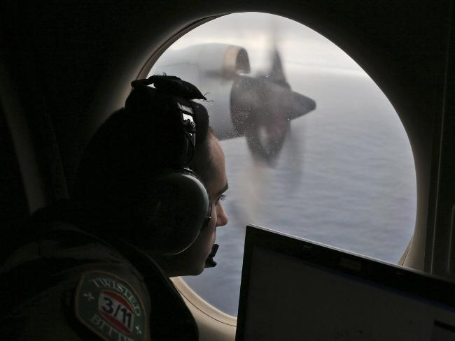 Flight officer Rayan Gharazeddine scans the water in the southern Indian Ocean off Australia from a Royal Australian Air Force AP-3C Orion during a search in March 2014. Picture: AP/Rob Griffith