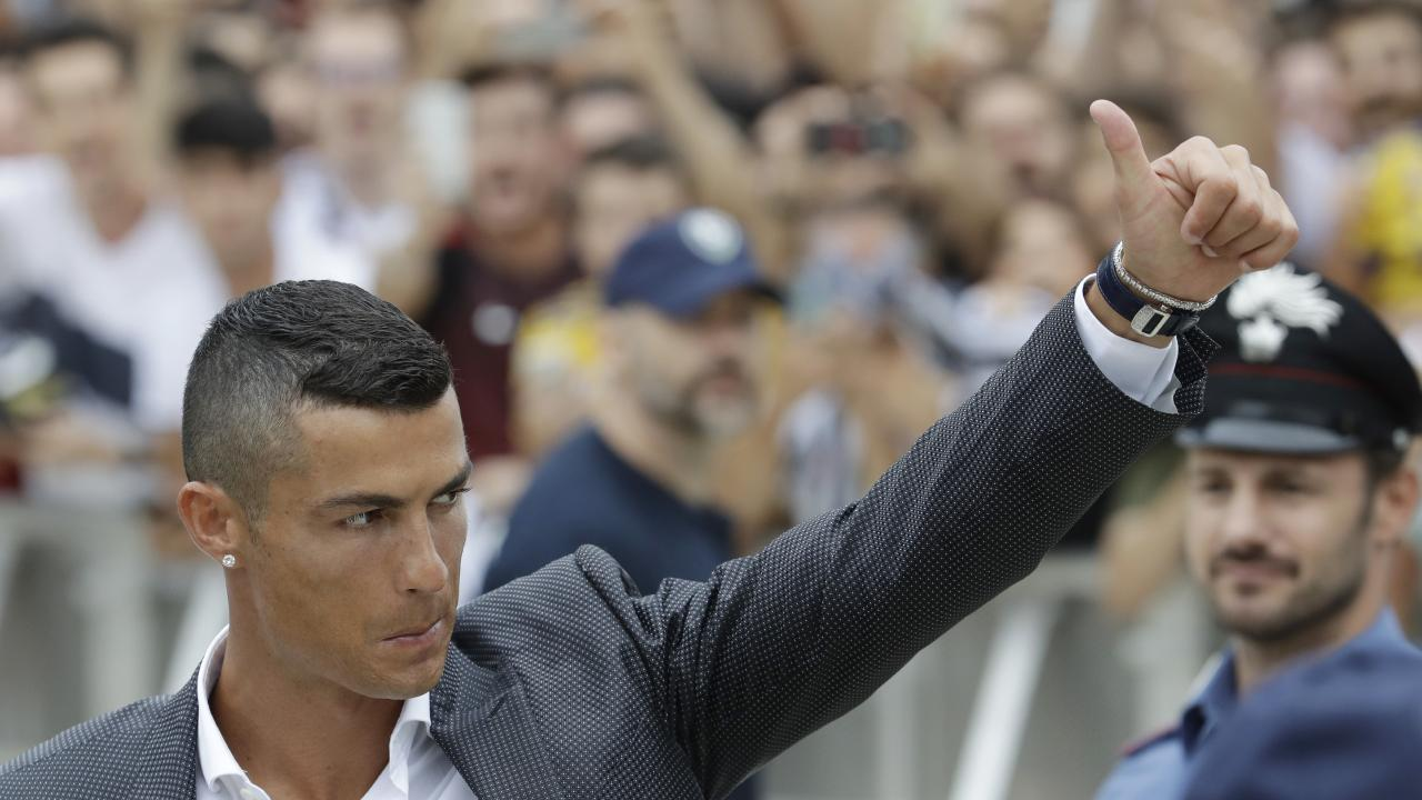 Portuguese ace Ronaldo gives the thumb-up sign as he arrives to undergo medical checks at the Juventus stadium in Turin.