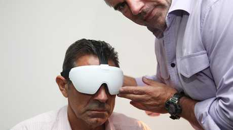 Dr Adrian Cohen tests former NFL Footballer Colin Scotts with a concussion device. Picture: Phil Hillyard