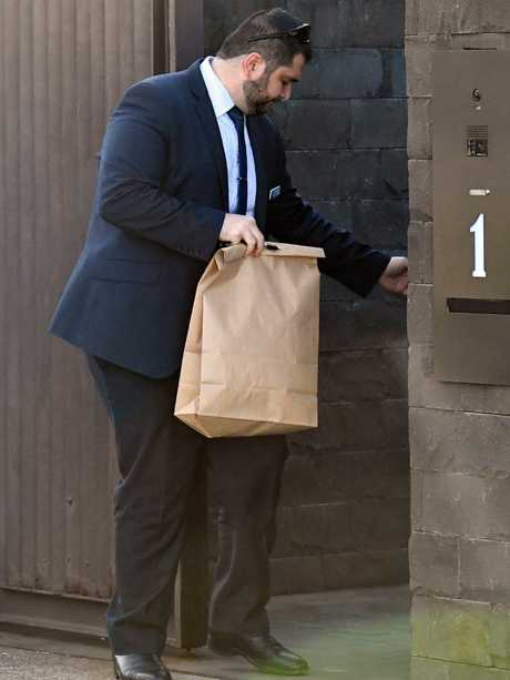 NSW Police detectives hold an evidence bag as they leave John Ibrahim's mansion. Picture: AAP