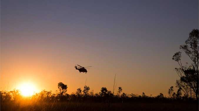 An Army helicopter flies at sunset.