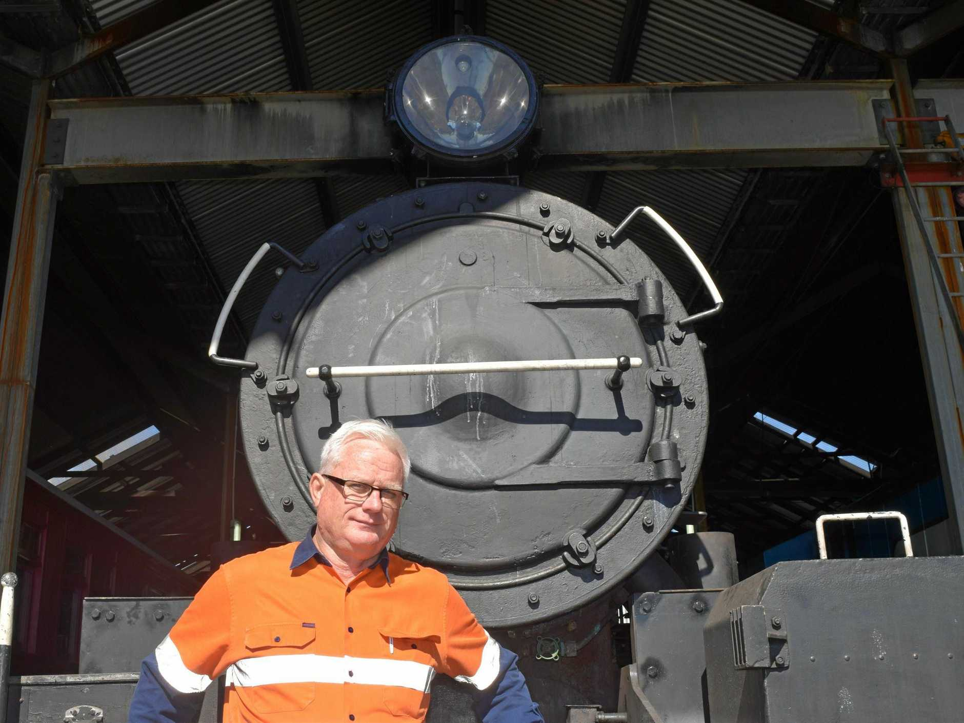 Mr Hurley stands with the iconic 'brown bomber' steam locomotive.