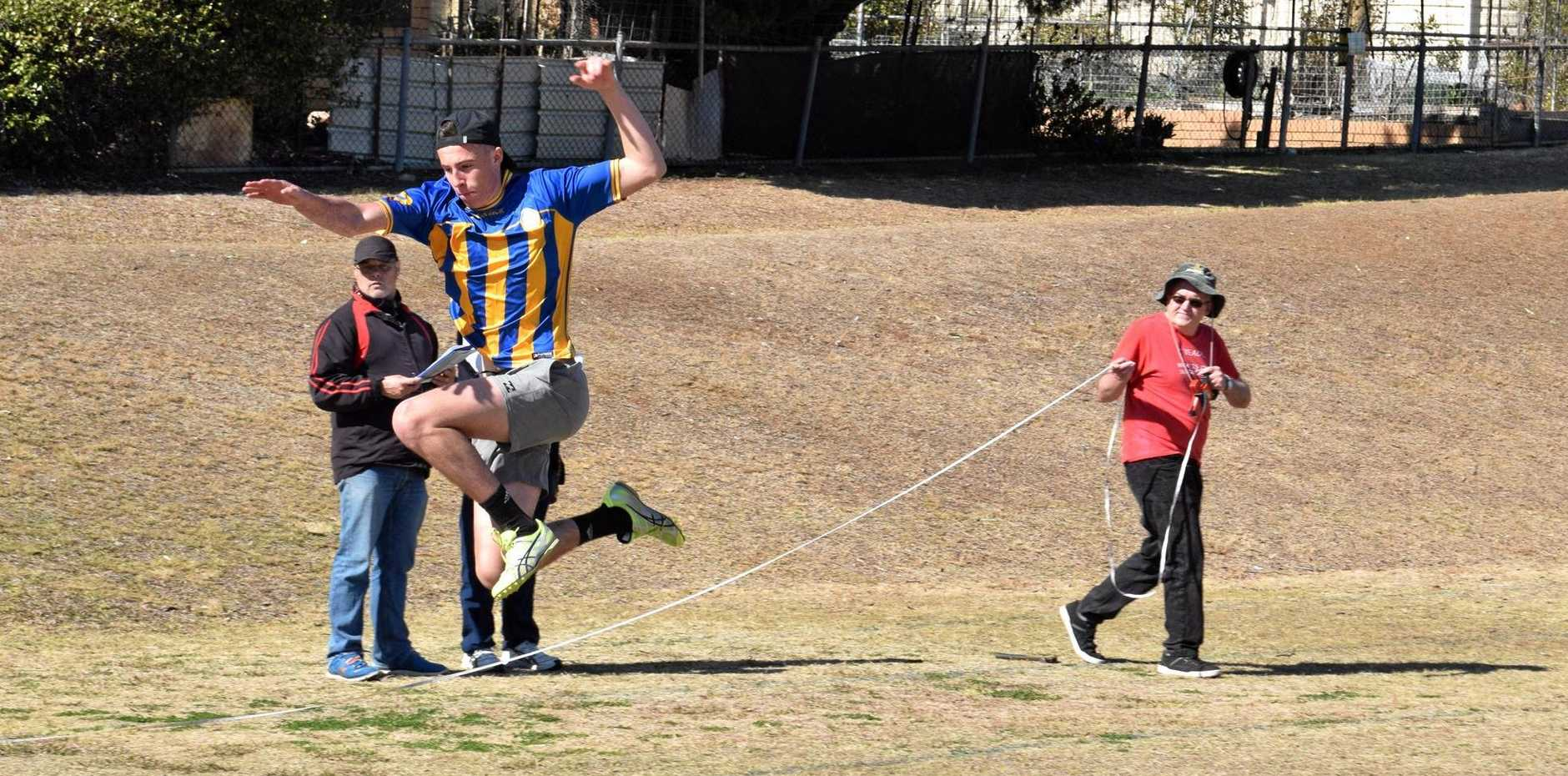 Devon Cooper caught mid-air in the Senior's Triple Jump.