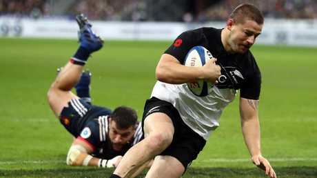 Dane Coles of New Zealand scores a try against France.