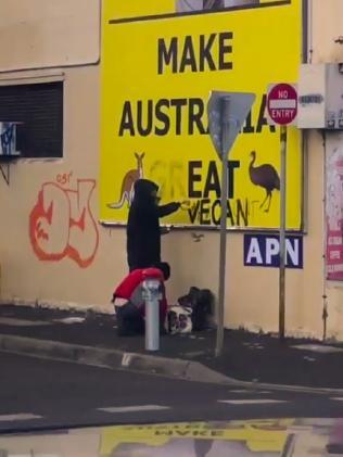 Vegans alter a Clive Palmer billboard.