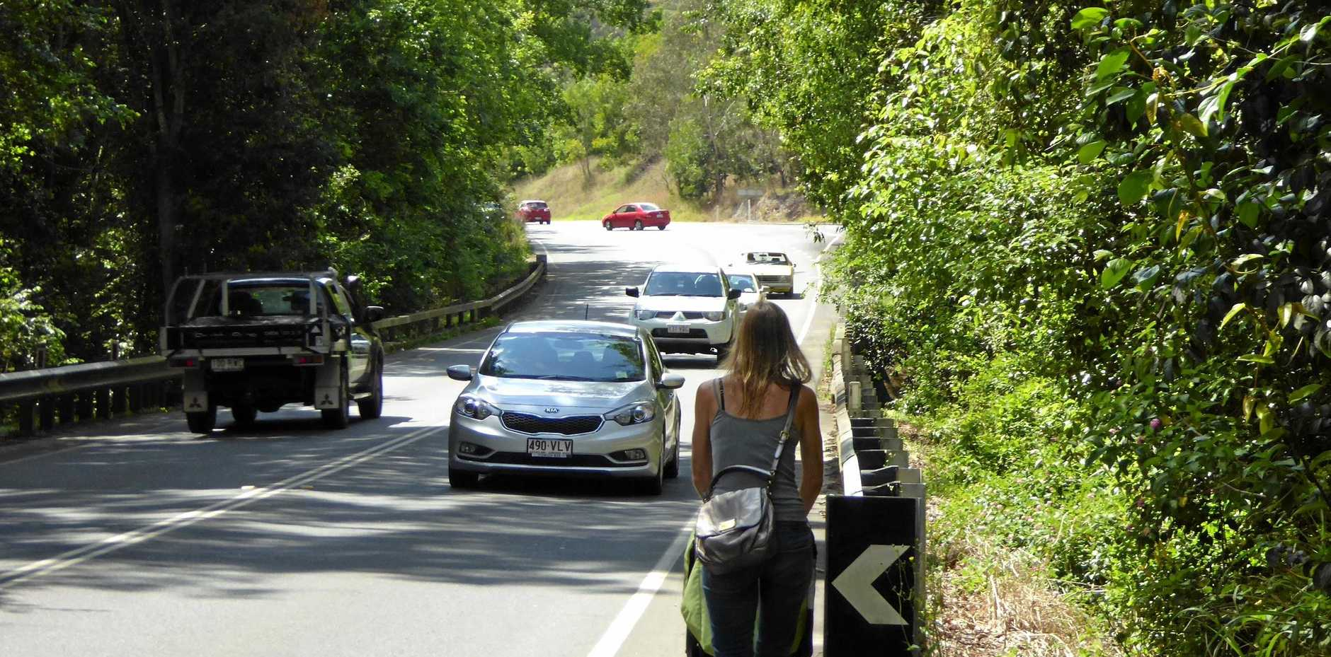 A pedestrian crosses a bridge on Eumundi Noosa Road that is shared with traffic.