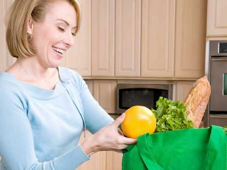 People in Canberra have been forced to remember their reusable bags for seven years and they're as fine with it as this lady is with her orange.