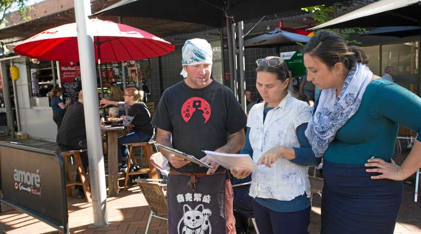 MamaGOTO owner Heath Keizer hands the petition to Councillors Sally Townley and Tegan Swan.