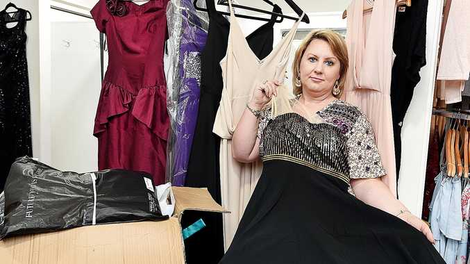 GLITZ AND GLAMOUR; Beautiful Elegance owner Annette Sutherland with donated formal dresses for farming families doing it tough during the drought.