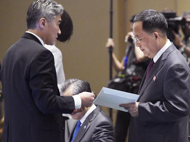 North Korean Foreign Minister Ri Yong Ho, right, receives an envelope from US Ambassador to the Philippines Sung Kim. Picture: AP