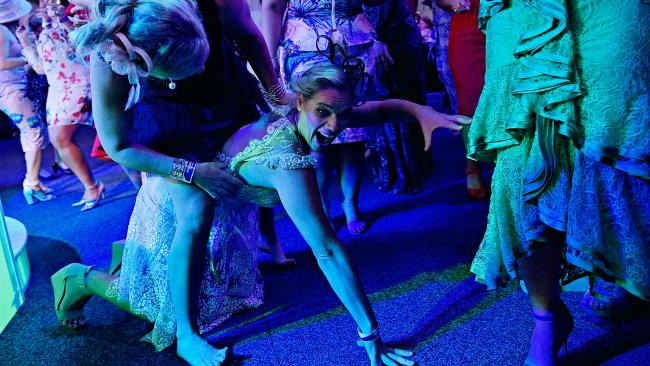 Caroline Anderson does the crocodile on the dance floor while being wrestled by a friend at the 2018 Bridge Toyota Ladies Day during the Darwin Cup Carnival.