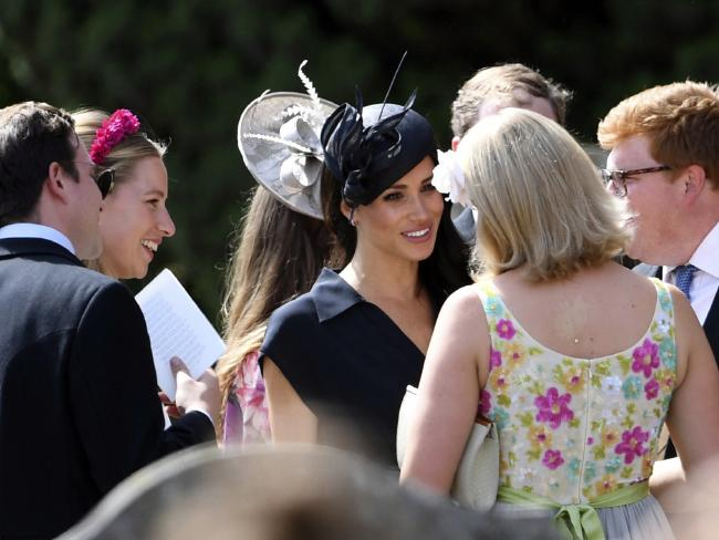 The Duchess of Sussex mingles with guests as she arrives at the wedding of husband Harry's childhood friend Charlie van Straubenzee. Picture: AP