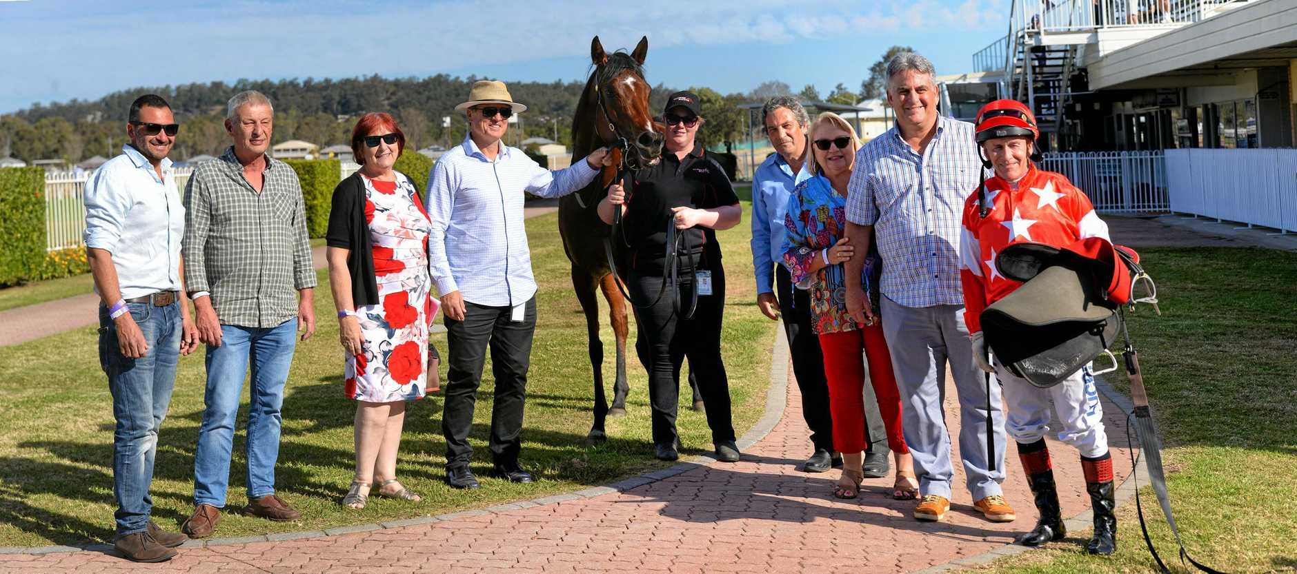 WINNING LINE-UP: Connections of Hold the Line join treble-winning jockey Jeff Lloyd at Ipswich Racetrack on Wednesday.