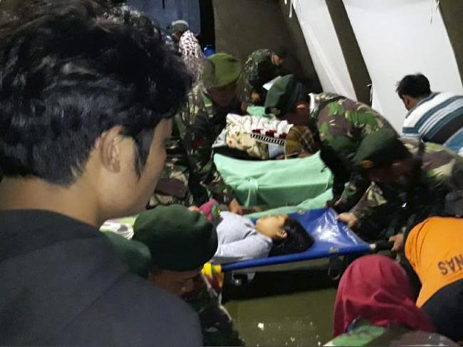 Indonesian soldiers tend to the injured. Picture: AP