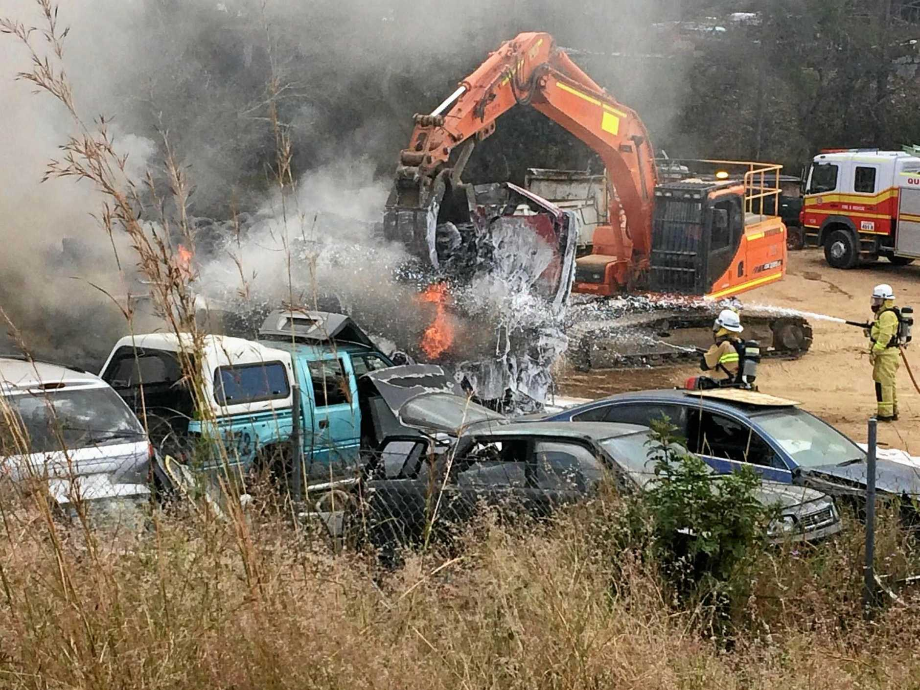 BIG BLAZE: Heavy machinery was used to help separate cars on fire during a large fire at a Gympie wrecking yard.