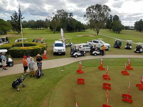 Orange ladies and sponsor's cars at the Maryborough Golf Club.