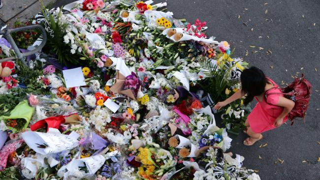 A mourner places flowers at the Brisbane CBD park where Eunji Ban's body was found. Picture: Darren England