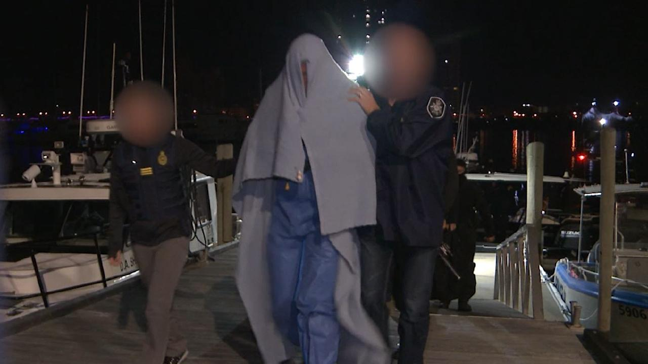 Police lead one of the alleged offenders away. Picture: AFP Media
