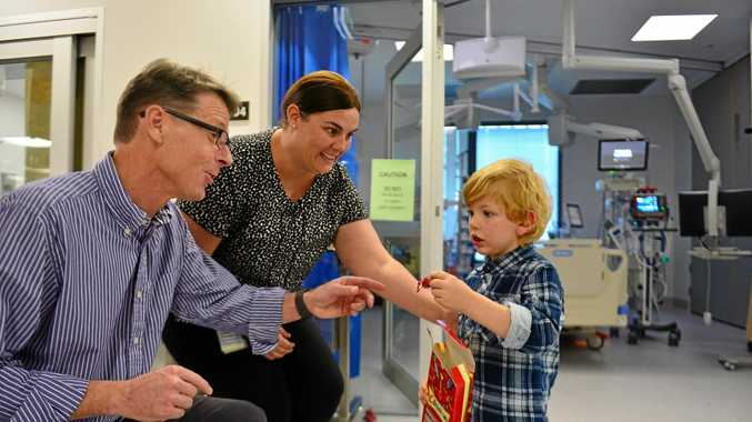 ONE FOR YOU: Emerson Kirkland, 3, hands out chocolates to Dr Peter Prager and Lauren Morgan, who helped him recover at Sunshine Coast University Hospital after a life-threatening seizure.