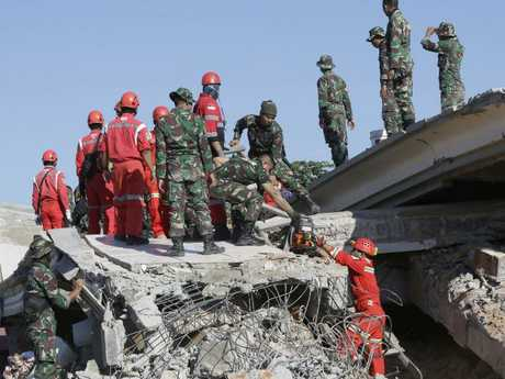 Rescuer teams working to locate victims trapped beneath rubble. Picture: AP Photo/Tatan Syuflana