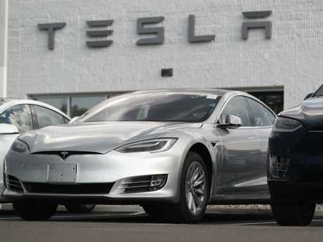 A2018 Model 3 sedan sits next to a Model X on display outside a Tesla showroom in Littleton Colorado. Board members at Tesla are evaluating CEO and Chairman Elon Musk's $70 billion proposal to take the electric car and solar panel maker private. Pictur