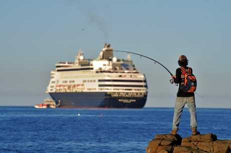 Daniel Johnson tries his luck at fishing on the rocks at Alexandra Headland as the cruise ship Pacific Eden is off the coast.