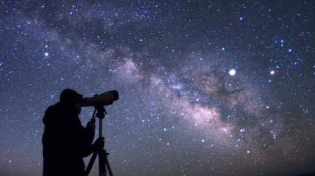 An observer and the spectacular appearance of our Milky Way galaxy, as seen from a very dark site.