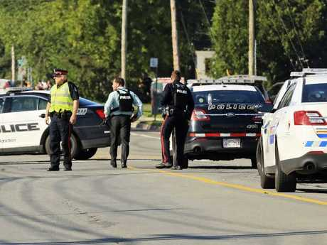 Police and RCMP officers survey the area of a shooting in Fredericton, New Brunswick, Canada.  Picture:  AP