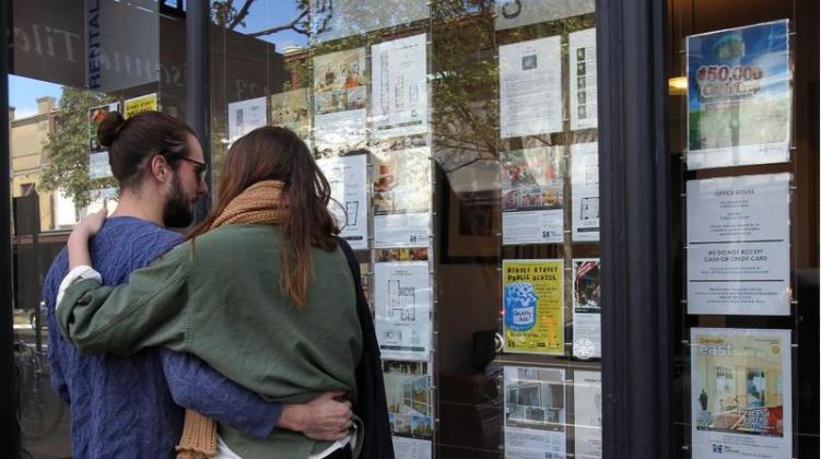 A couple looking at homes for sale in a real estate agency window.