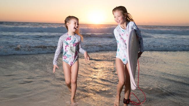 Billie Berg, 5, and sister Mila, 7, enjoy a sunrise surf at Froggy's Beach near the NSW border. Picture: Luke Marsden.