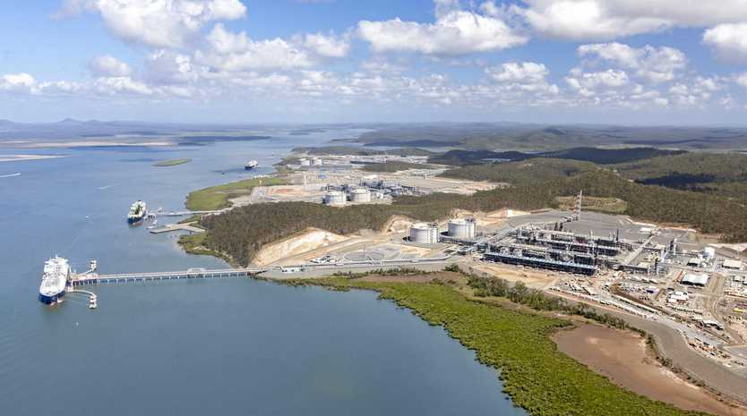 An aerial view of the three LNG projects on Curtis Island all with ships at their jetties.