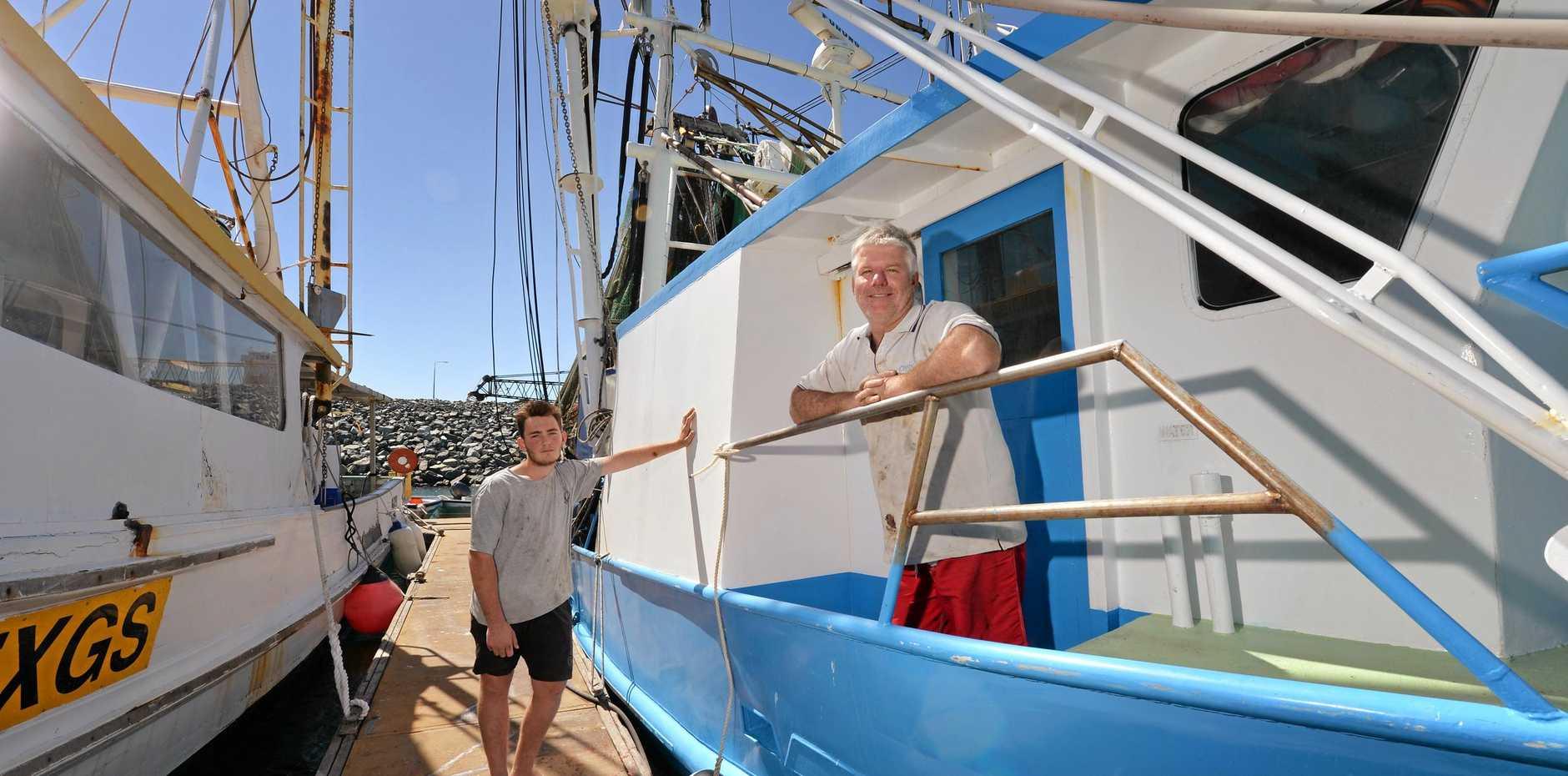 Warren Dean, operator of Bowen-based prawn trawler Tweed Seeker and deckhand Camen McMillan take a break to refuel at Mackay yesterday.