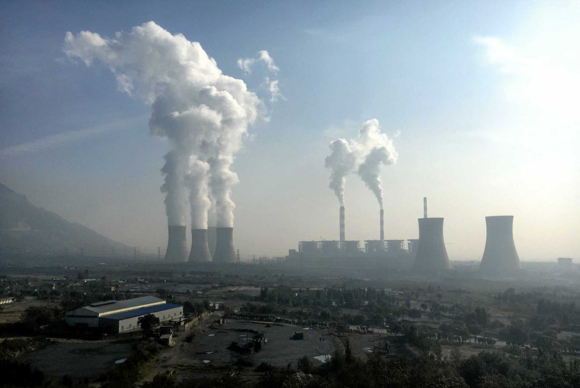 Smoke and steam are discharged from chimneys and cooling towers at a coal-fired power plant in Jiyuan city, central China's Henan province, 30 October 2016.