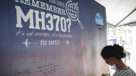 A girl writes a condolence message during the Day of Remembrance for MH370 earlier this year. (Pic: Vincent Thian/AFP)