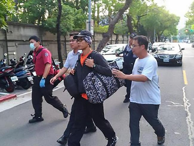 Chou is taken away by police as members of the public walk alongside him to ensure he does not escape.