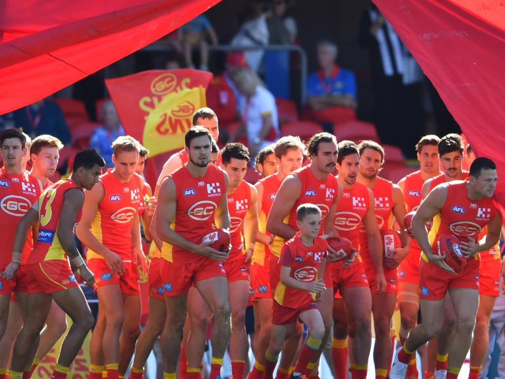 Suns players run through the banner before the Round 21 AFL match between the Gold Coast Suns and the Richmond Tigers at Metricon Stadium. Picture: AAP Image/Darren England.