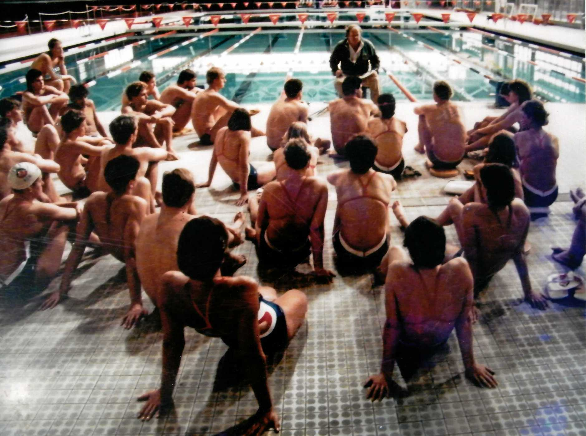Bill Sweetenham (head coach) holds a large on-deck meeting with his Australian Institute of Sport team.