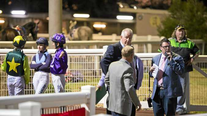 Racing officials and jockeys, including chief steward Rion Hitchener (right), wait for the all clear to get racing under way at Clifford Park last Saturday night.