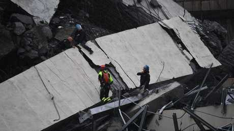 Rescue workers go through the debris of the collapsed bridge in Genoa.