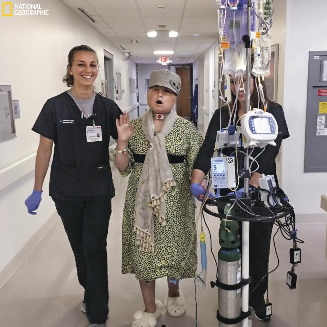 On one of her daily walks in the hospital, Katie sings as she exercises with physio Becky Vano (at left) and physio student Nicole Bliss. Picture: Maggie Steber/National Geographic
