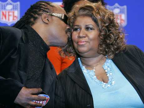 Singer Aretha Franklin (R) gets a kiss from Stevie Wonder during a news conference in Detroit in 2006. Picture: Supplied