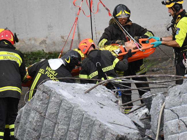 Firefighters rescue a person from the rubble of the collapsed Morandi highway bridge.