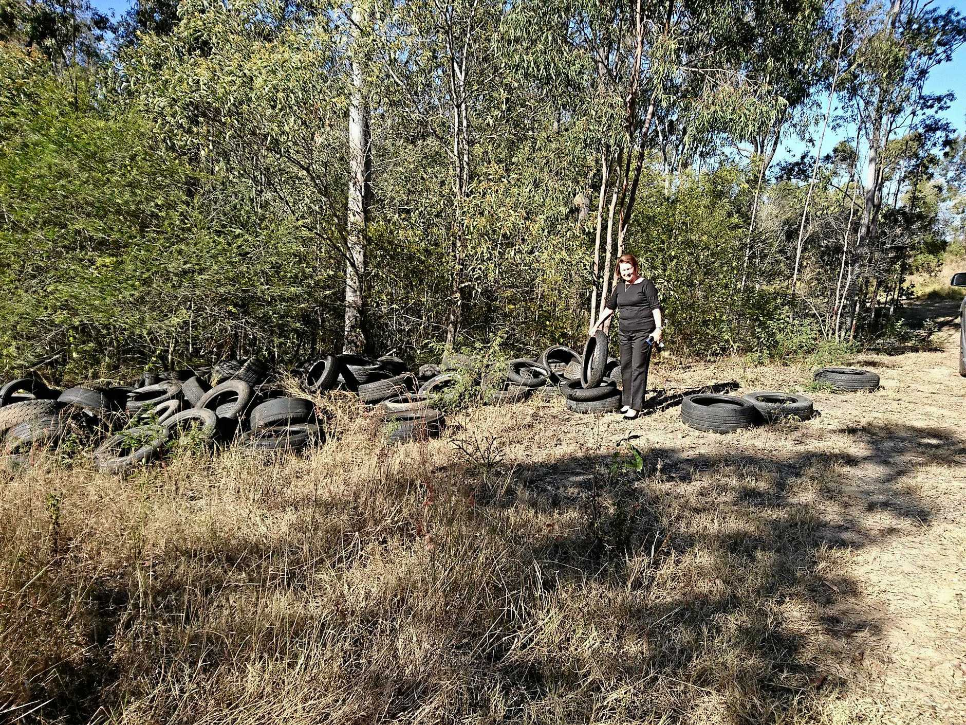 Cr Sheila Ireland with illegally dumped tyres found on Lakes Entrance Drive.
