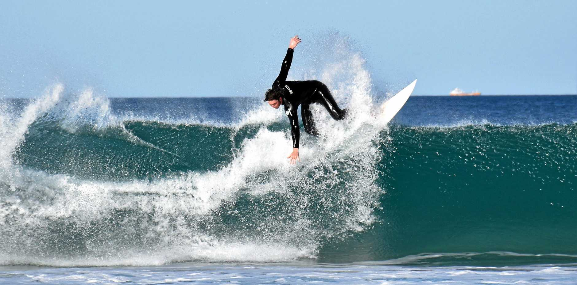 A surfer makes the most of the waves at Kawana on the weekend.