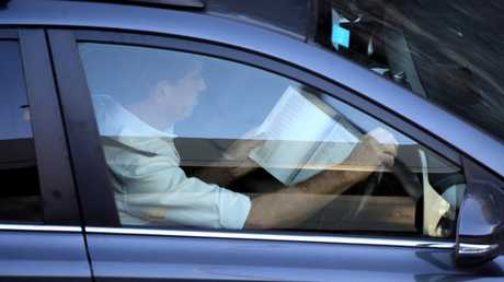 Catching up with reading on Manly Rd yesterday. Picture: John Grainger