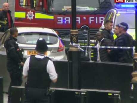 Armed police surrounded a car and arrested a man after a number of pedestrians were hit before ploughing into security barriers outside Parliament in Westminster, London. Picture: Sky TV