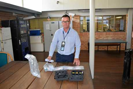 DRUG BUST: Detective Senior Constable David Price displays some of the drugs and two of the tasers seized by police attached to the Maryborough CIB on Thursday. A 33-year-old man and 25-year-old woman will face court over the bust.