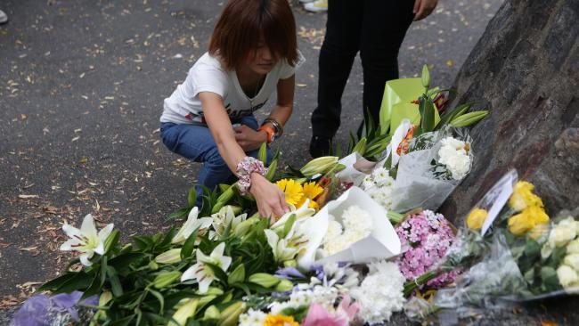 A woman lays flowers at the site where Eunji Ban was found. Picture: Tim Marsden