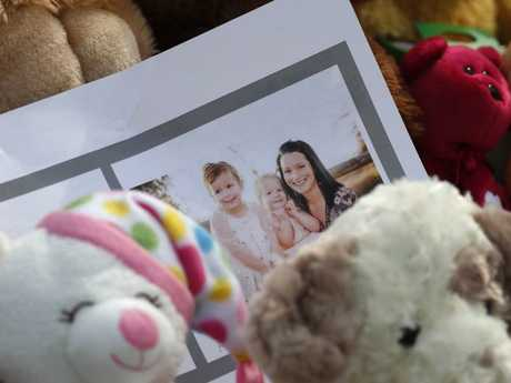 A photograph sits amid the tributes as they grow outside the home where a pregnant woman, Shanann Watts, and her two daughters, Bella and Celeste, lived. Picture: AP